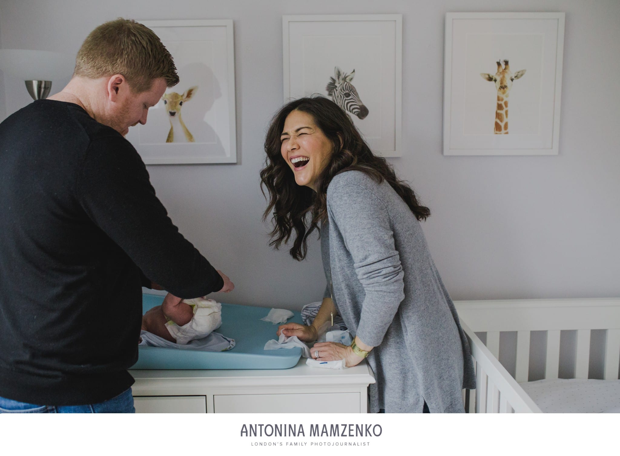 young family changing newborn's baby nappy laughing at home in Kensington, London