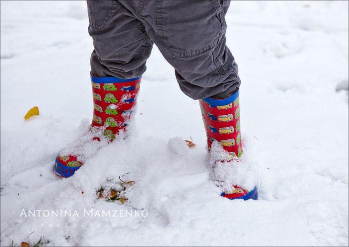 little boy wearing wellies in the snow