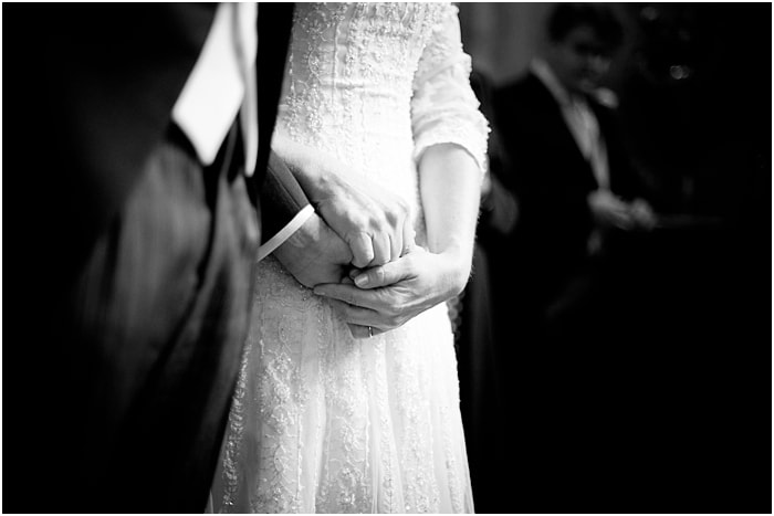 bride and groom holding hands tight during speeches, emotional
