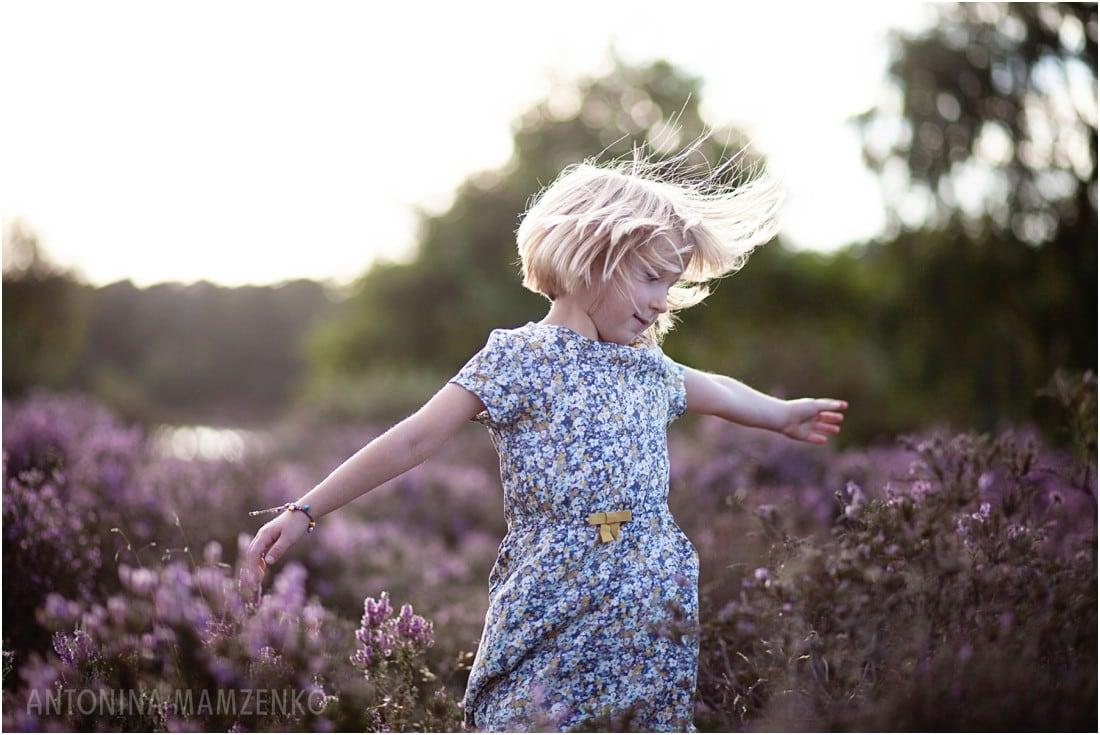 a girl dancing in field of heather near frensham ponds in surrey