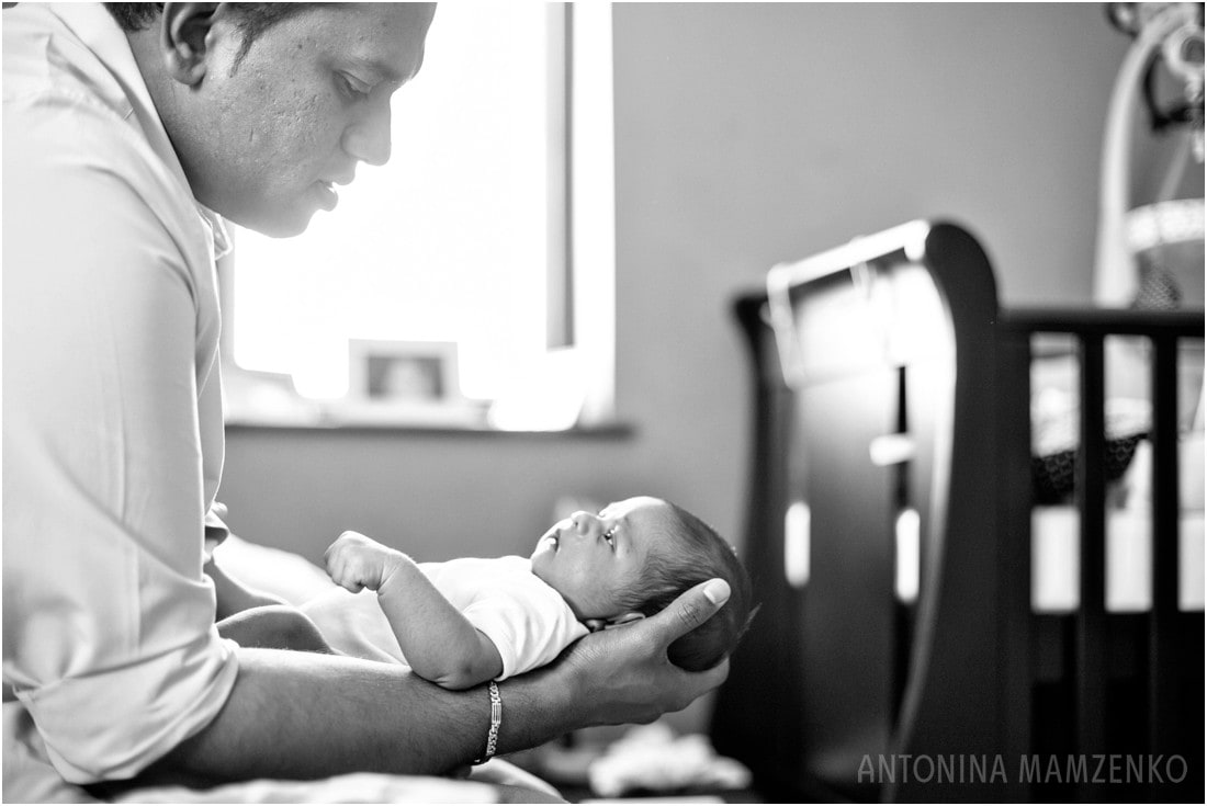 father holding newborn son in baby nursery - surrey newborn photographer