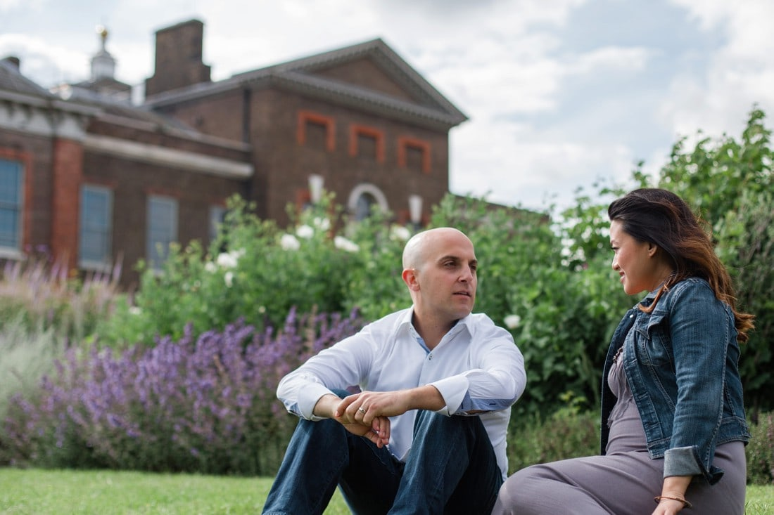 couple sitting on the grass in front of kensington palace