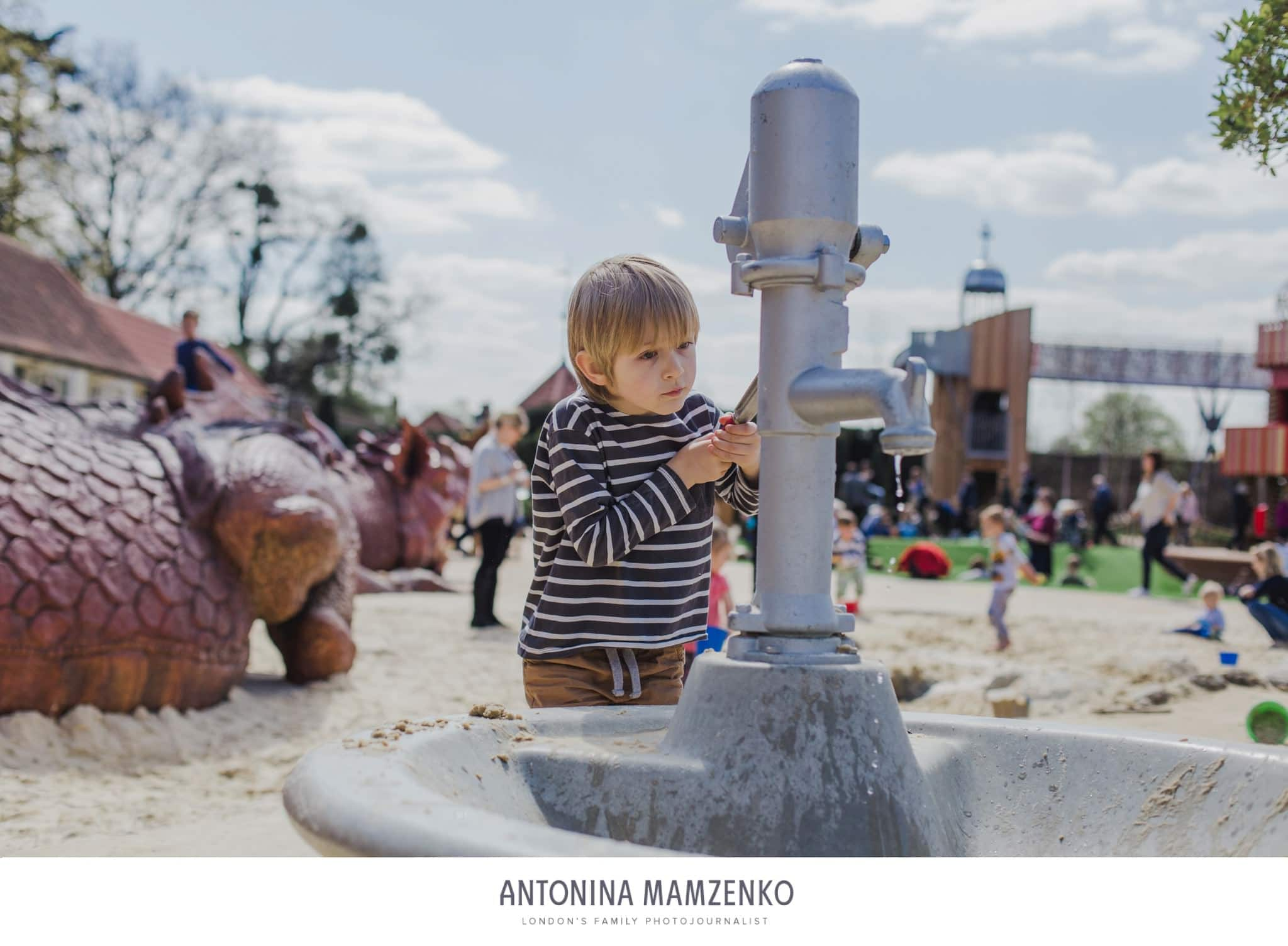 boy playing with a water fountain at Magic Garden playground in Hampton Court, Surrey