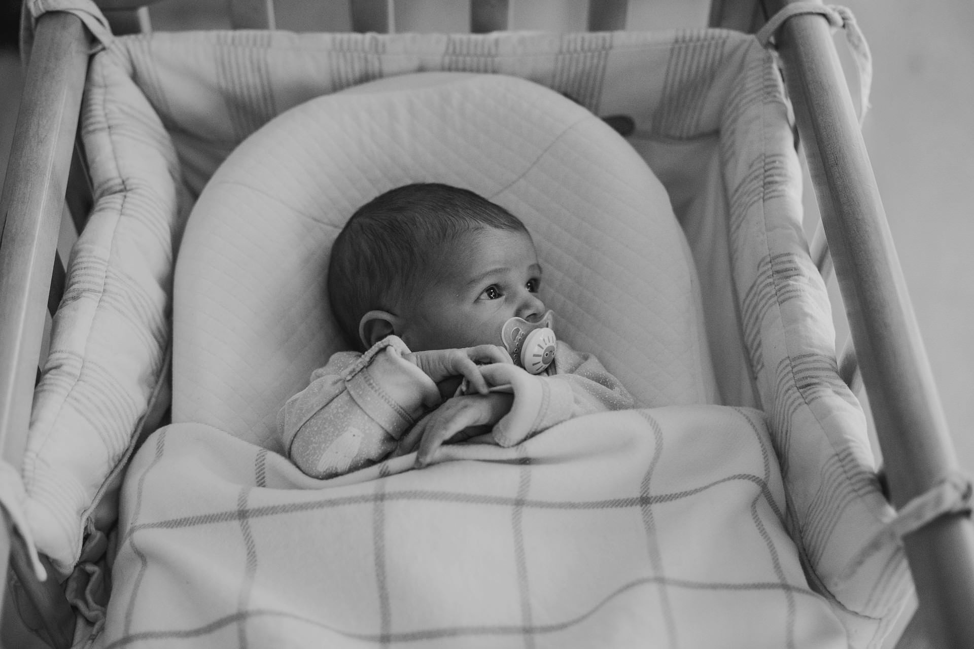 newborn baby in her cot with pacifier