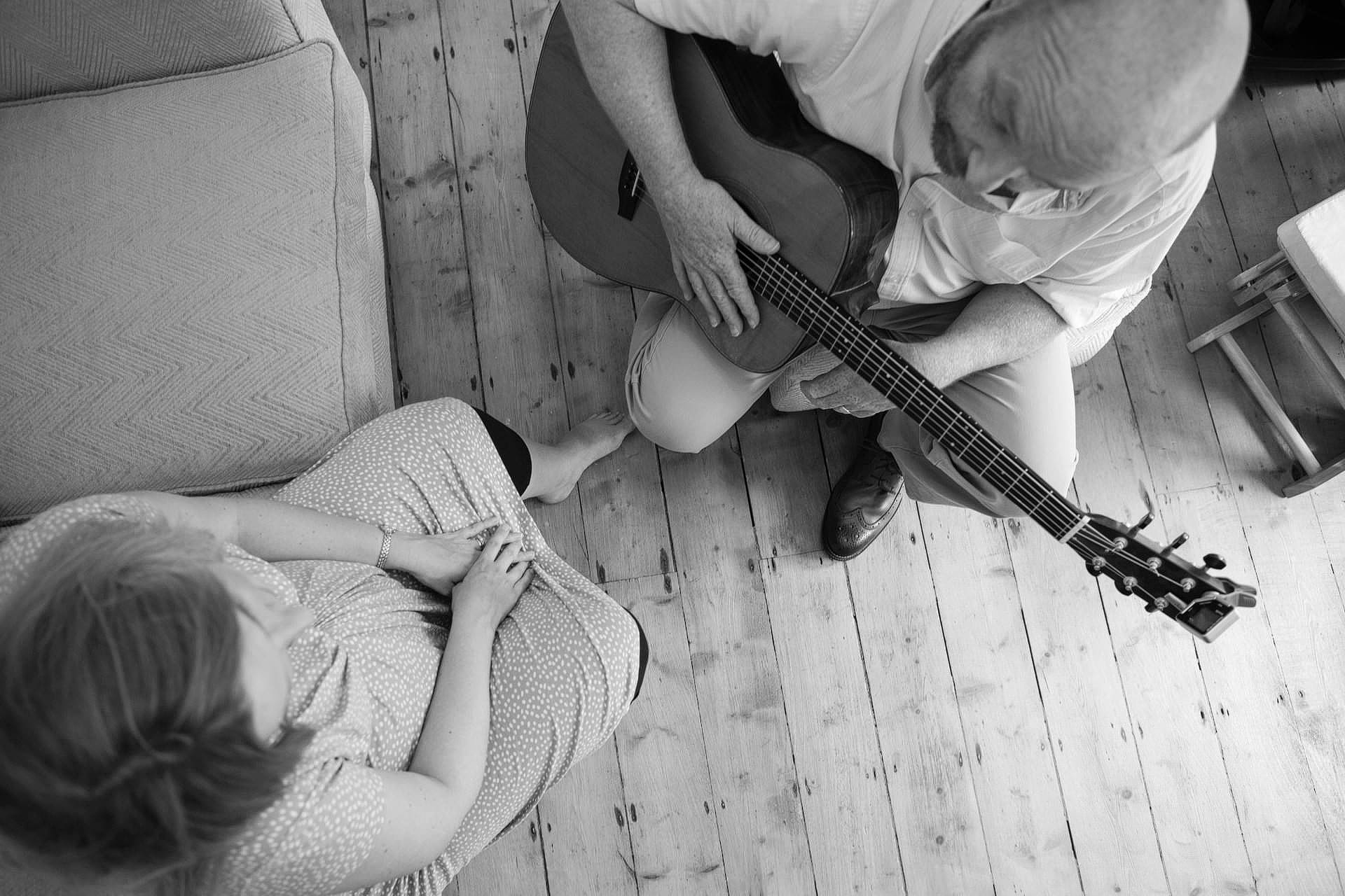 pregnant couple at home with dad-to-be playing guitar