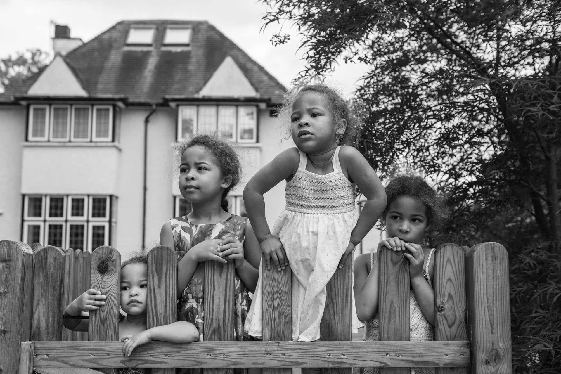 four sisters looking over the fence in their home in hampton, london