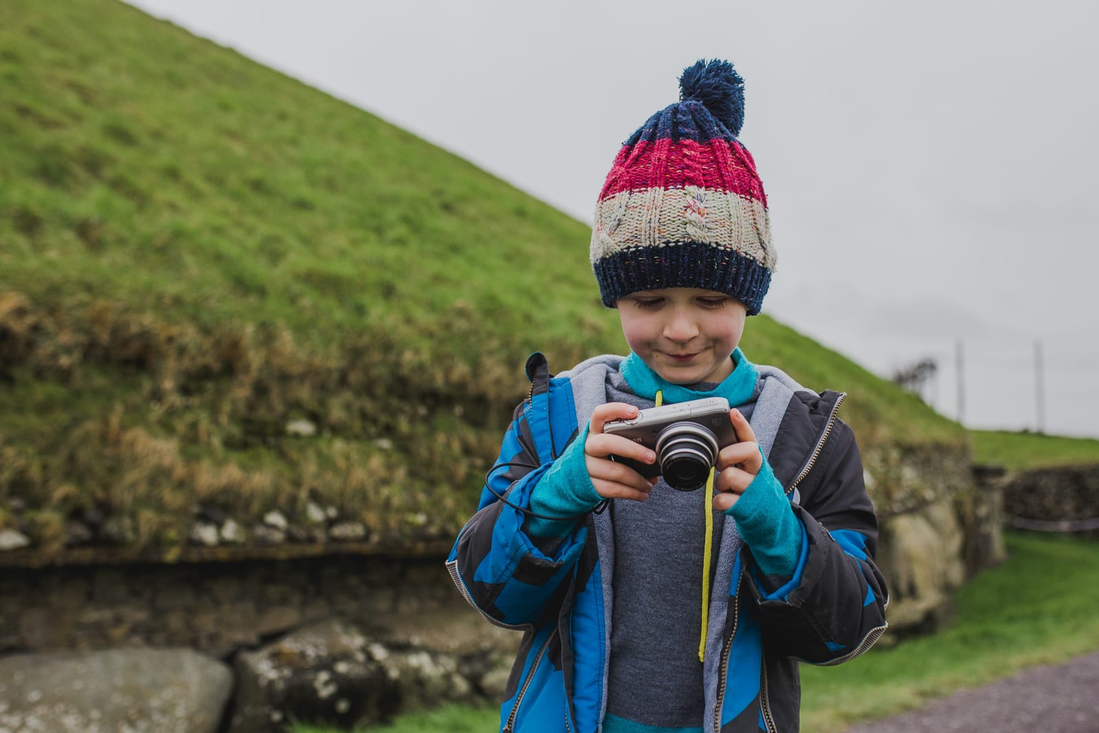 boy looking at a picture he took with his digital compact camera