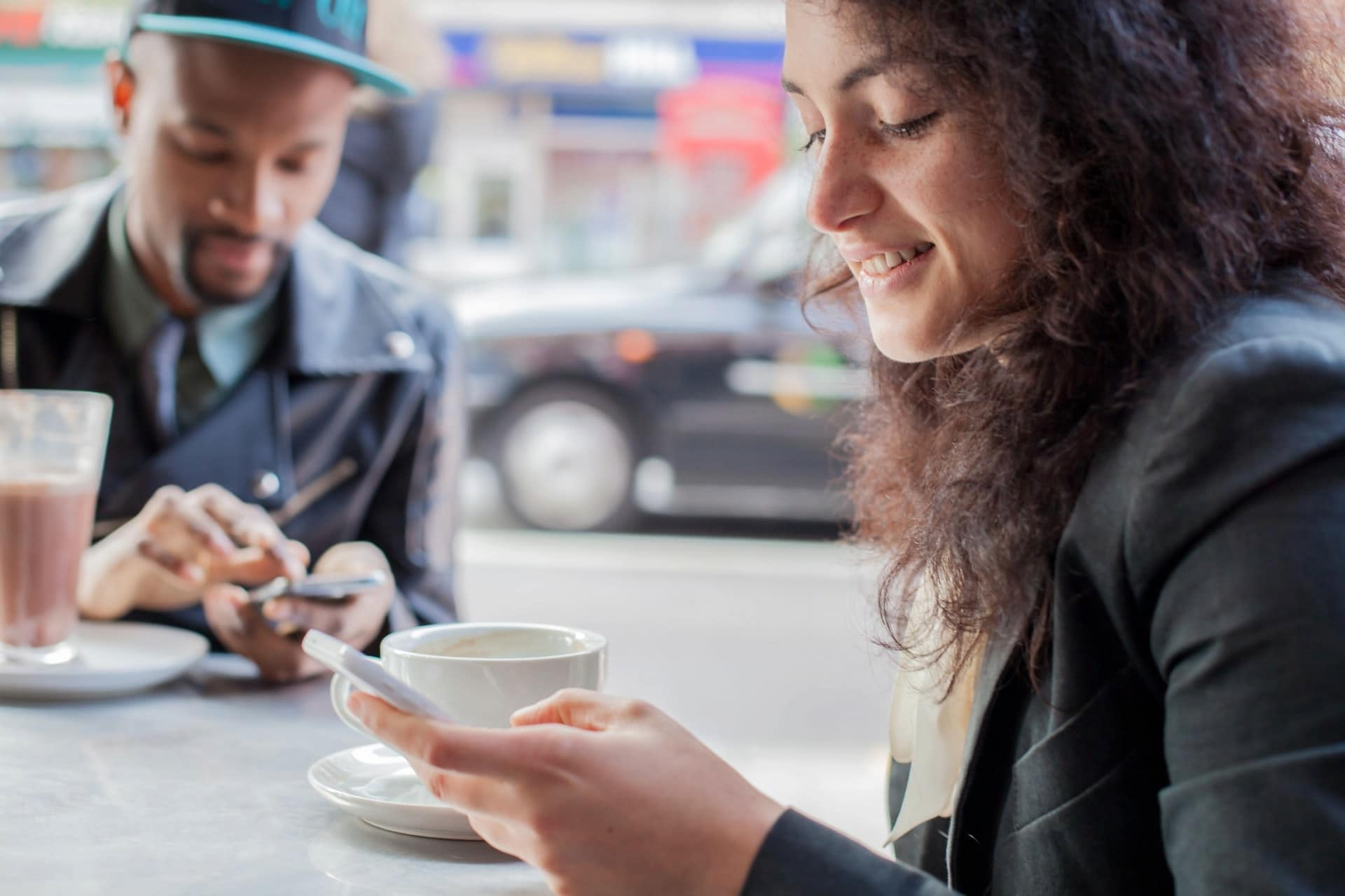 young couple looking at their mobile phones and drinking coffee