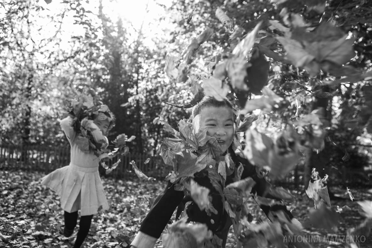 children throwing leaves at a photographer during a photoshoot in holland park