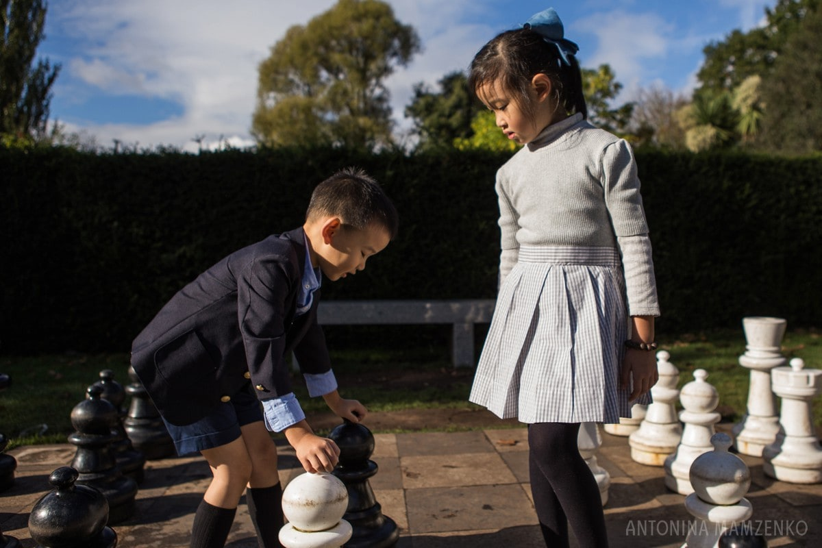 brother and sister playing chess in holland park