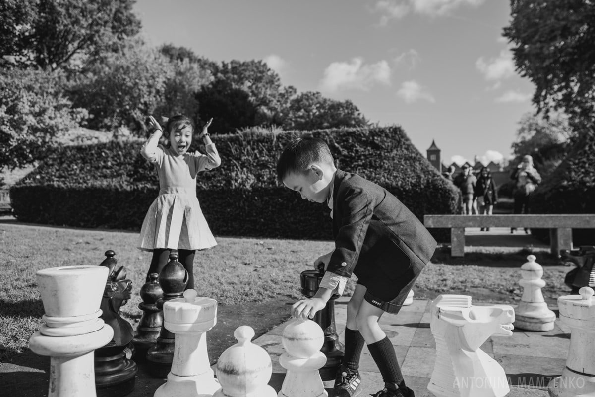 kids playing the giant chess set at holland park in notting hill