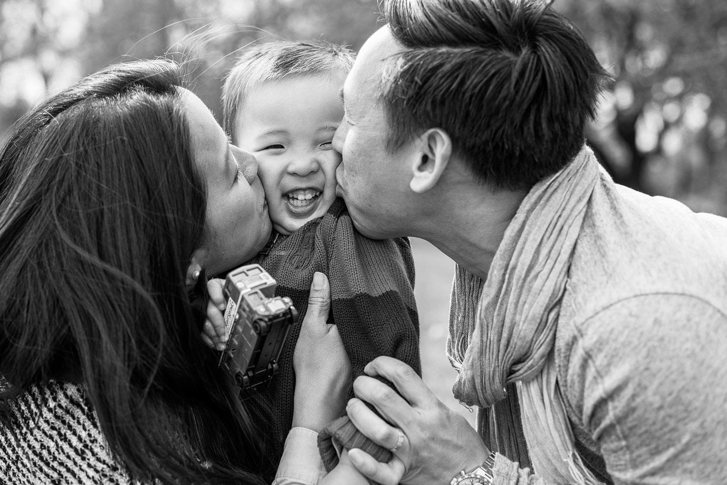 parents giving their son a sandwich kiss during a relaxed family photoshoot in fulham