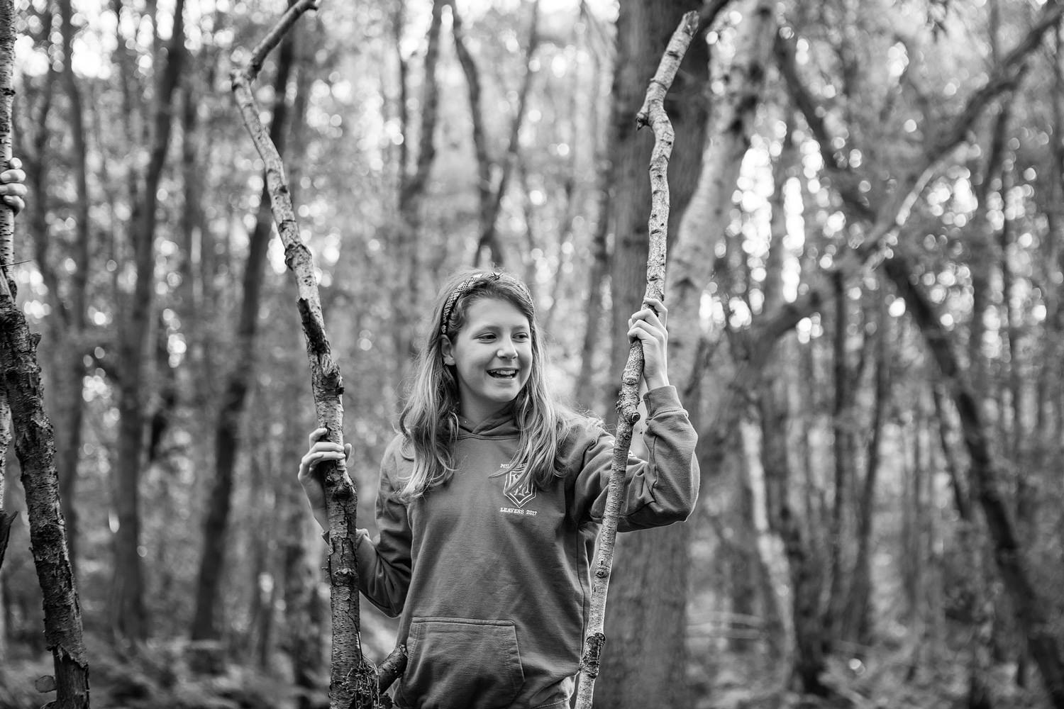 a black and white picture of a pre-teen girl helping to build a den in esher woods during a family photoshoot