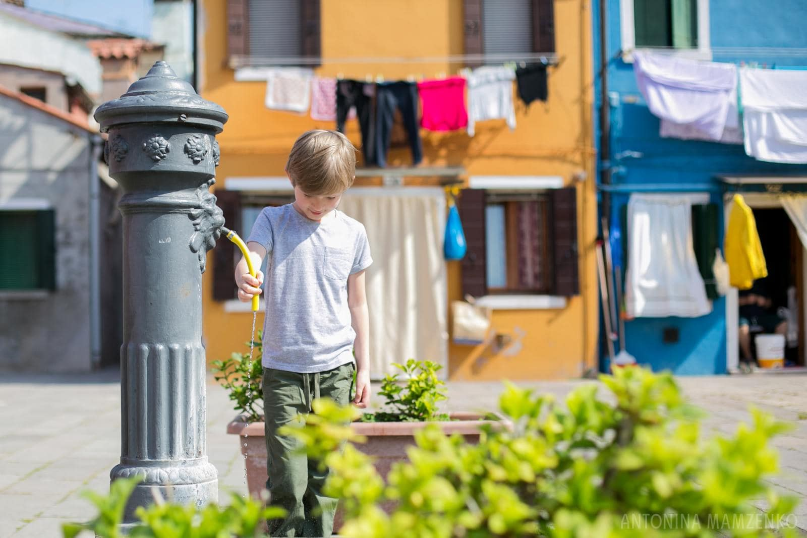 a boy drinking from water fountain in Burano, Venice, Italy