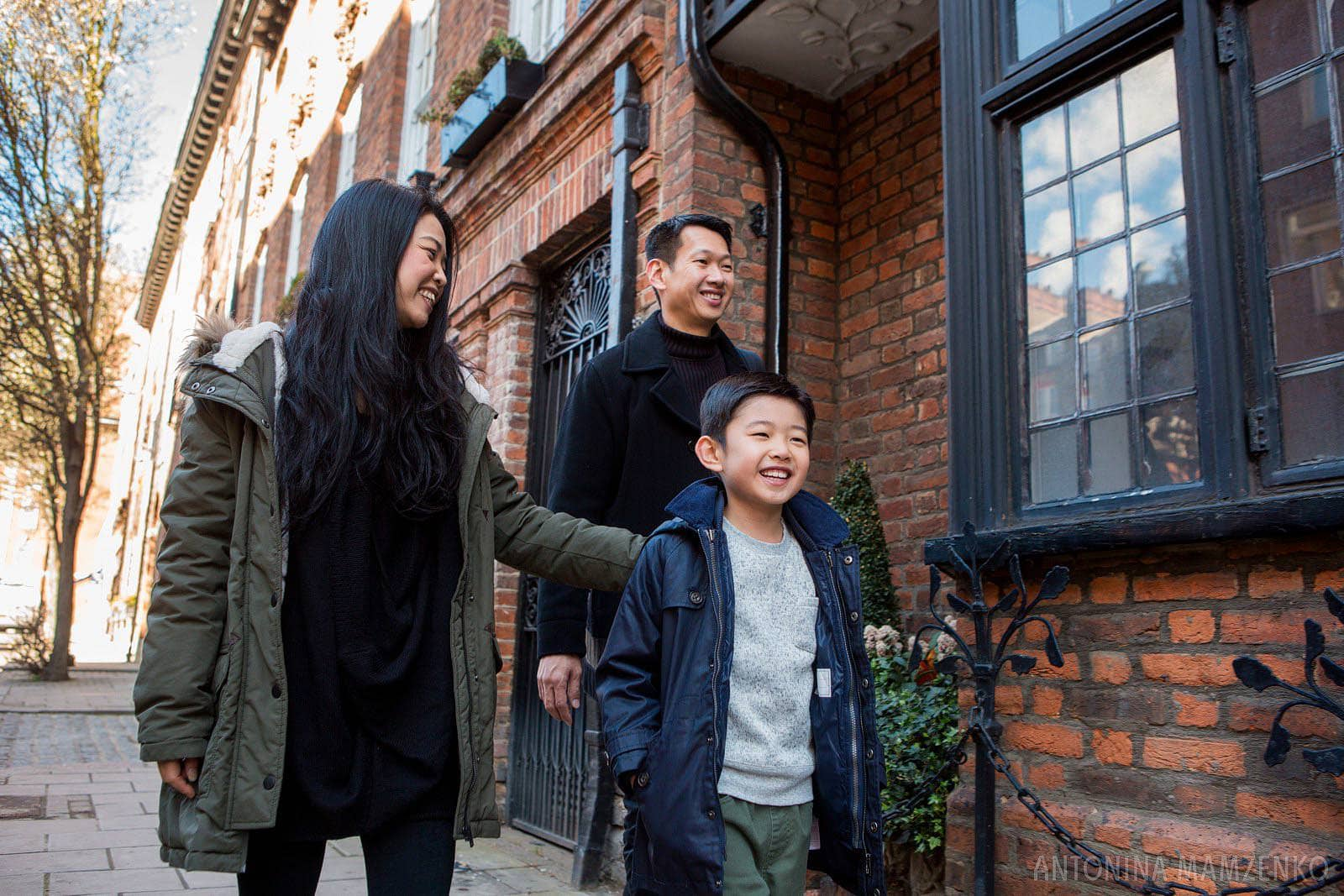 family from Hong Kong walking in Mayfair with red back buildings behind them