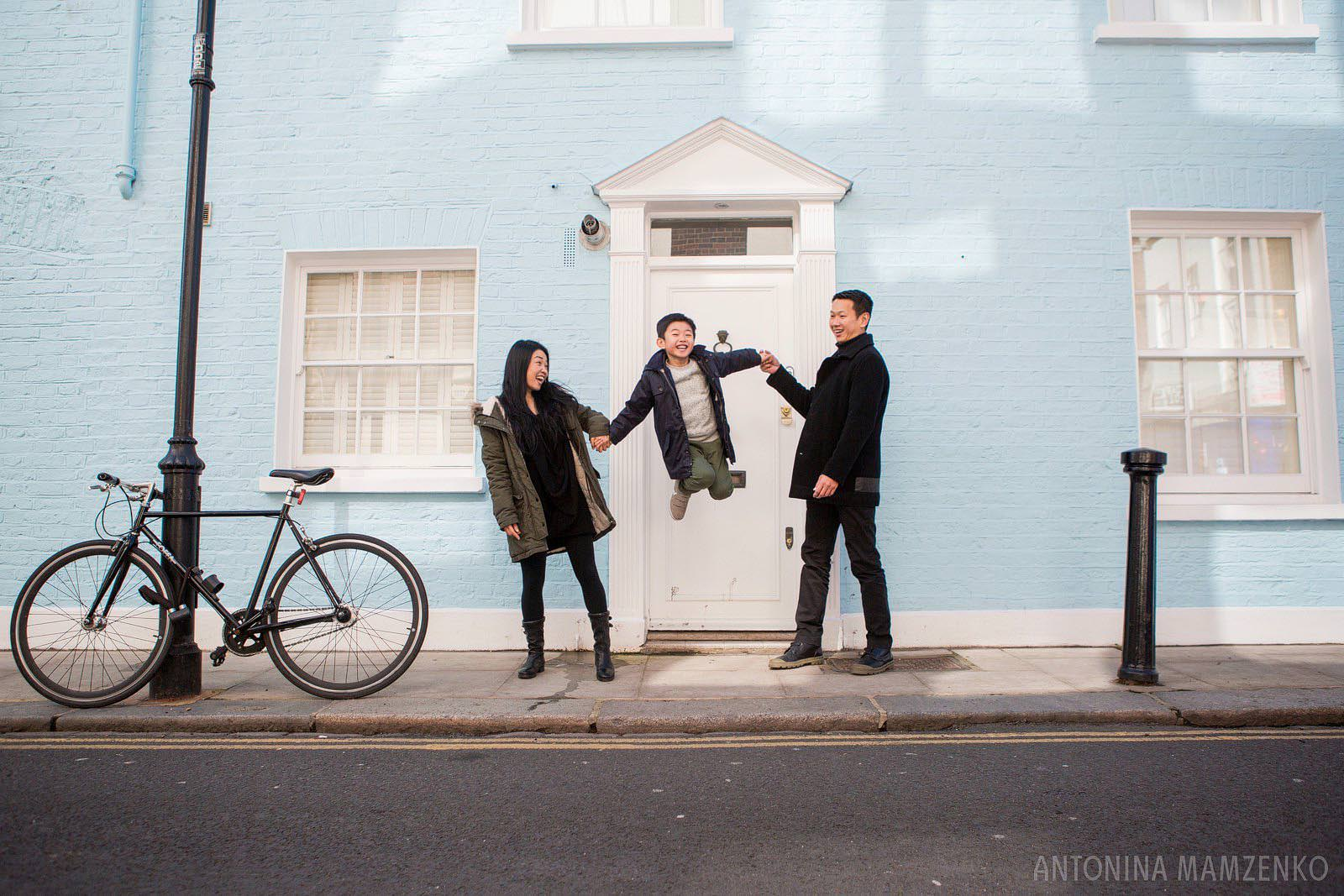 a family with a young boy playing in front of colourful houses in Notting Hill