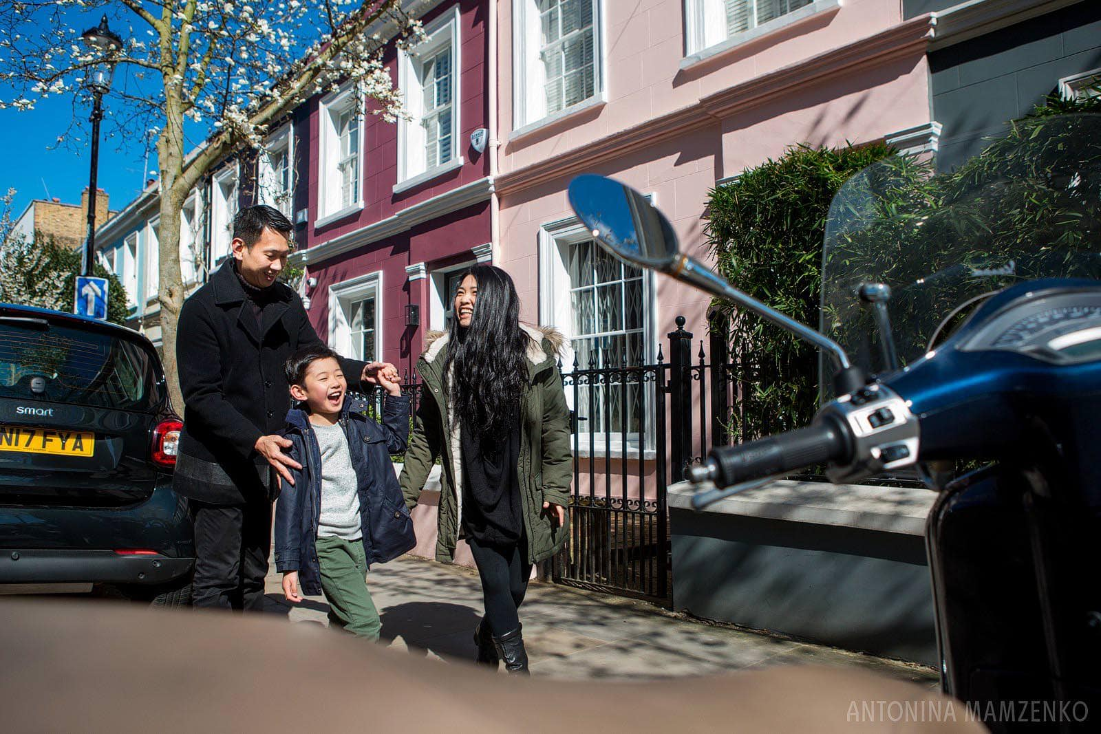a family enjoying their time together with colourful houses in Notting Hill providing a great backdrop to the photograph