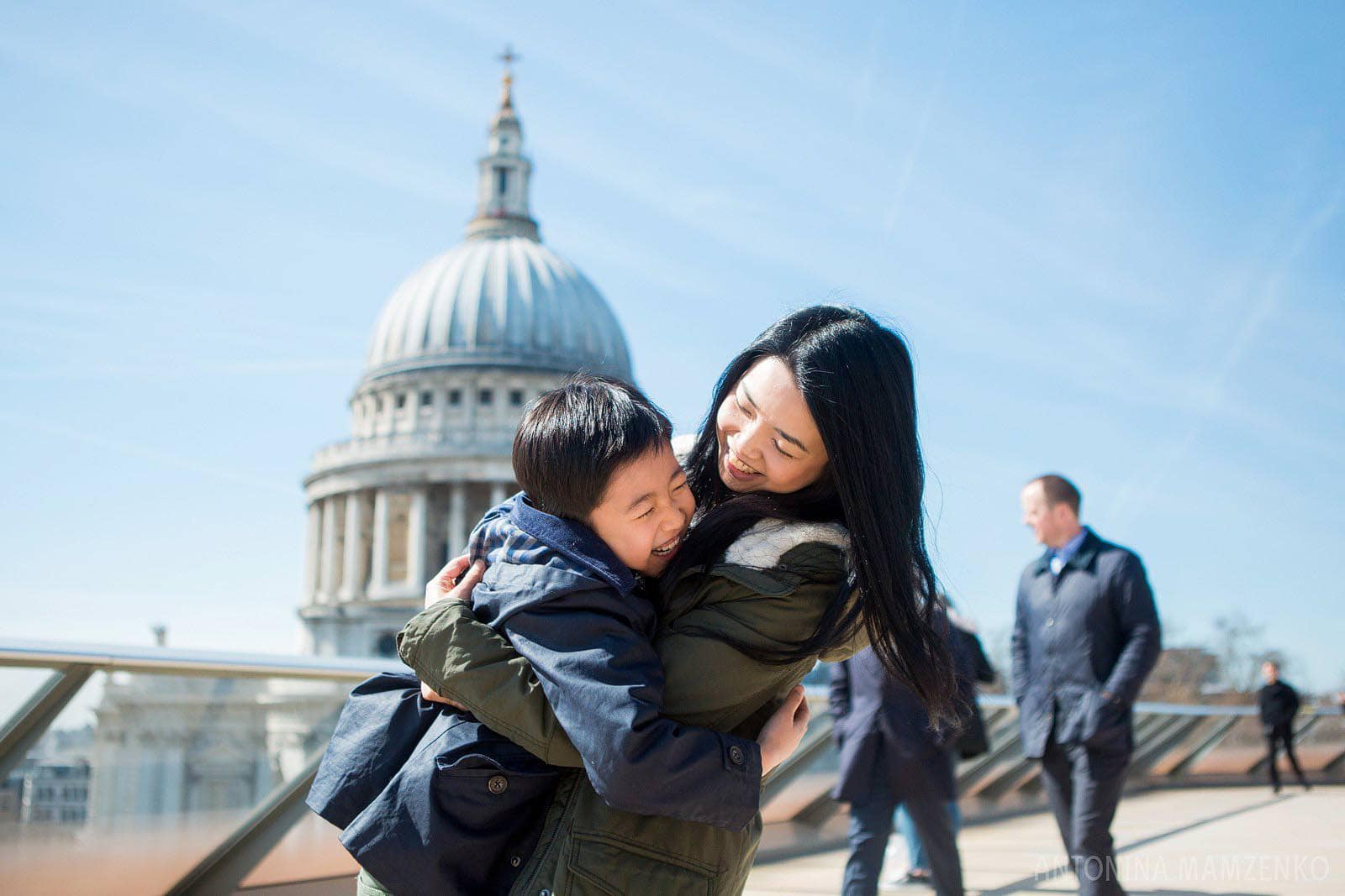 mother and sun hugging on a rooftop with St Paul's Cathedral in the background