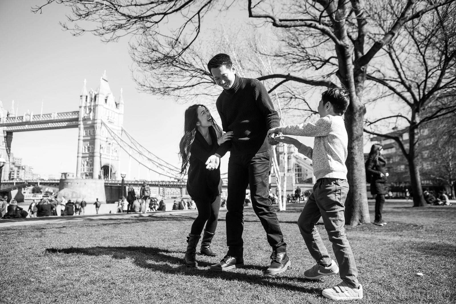 family playing during a vacation photoshoot with Tower Bridge in the background