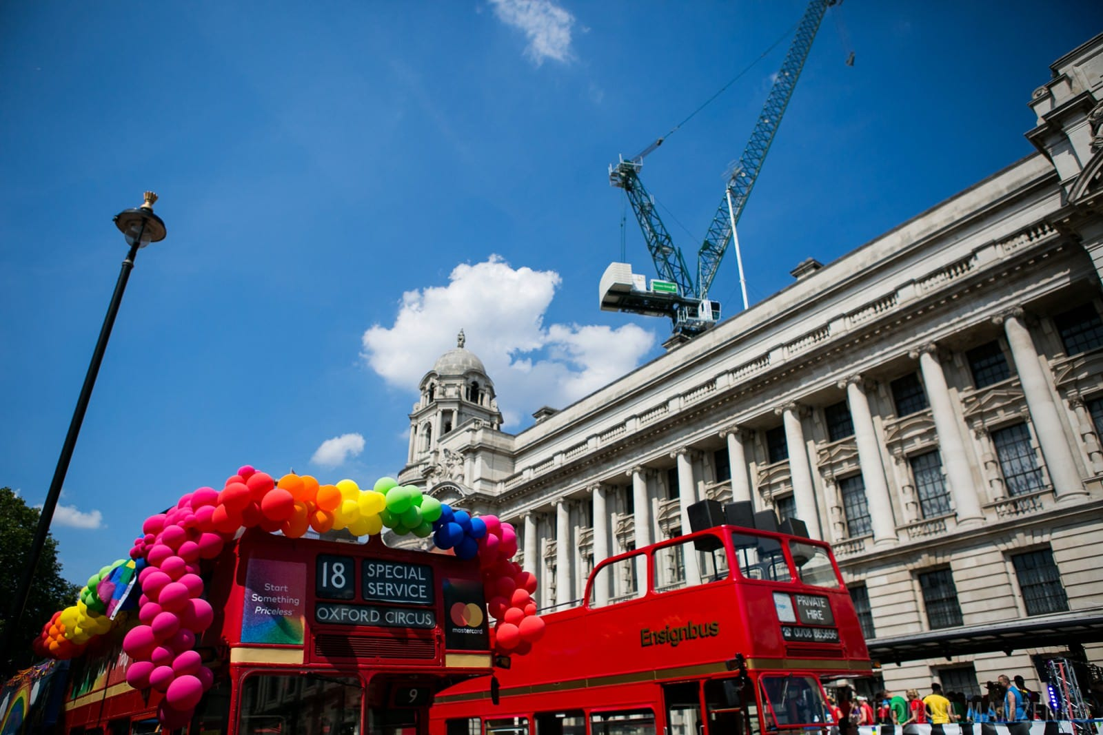 red buses decorated with balloons at the end of London Pride 2018 route