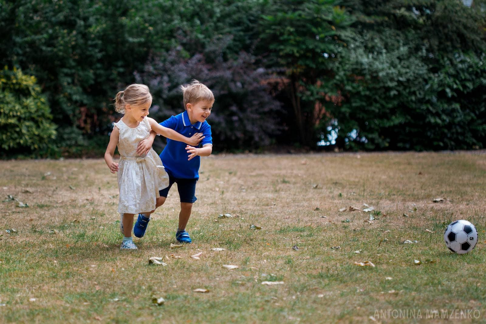 bother and sister playing football in a private gardens in chelsea, london