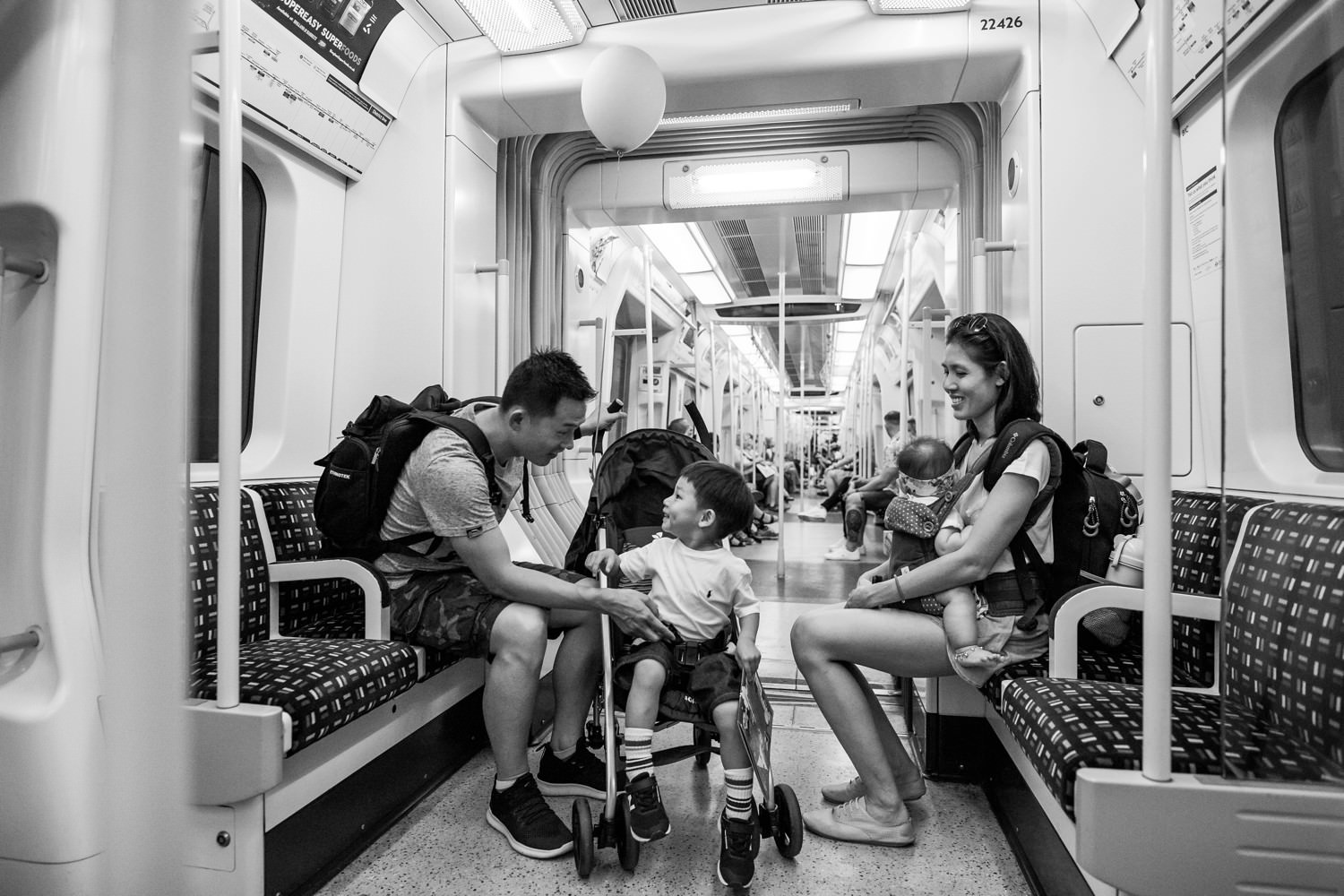 a black and white photograph of a family riding on London tube