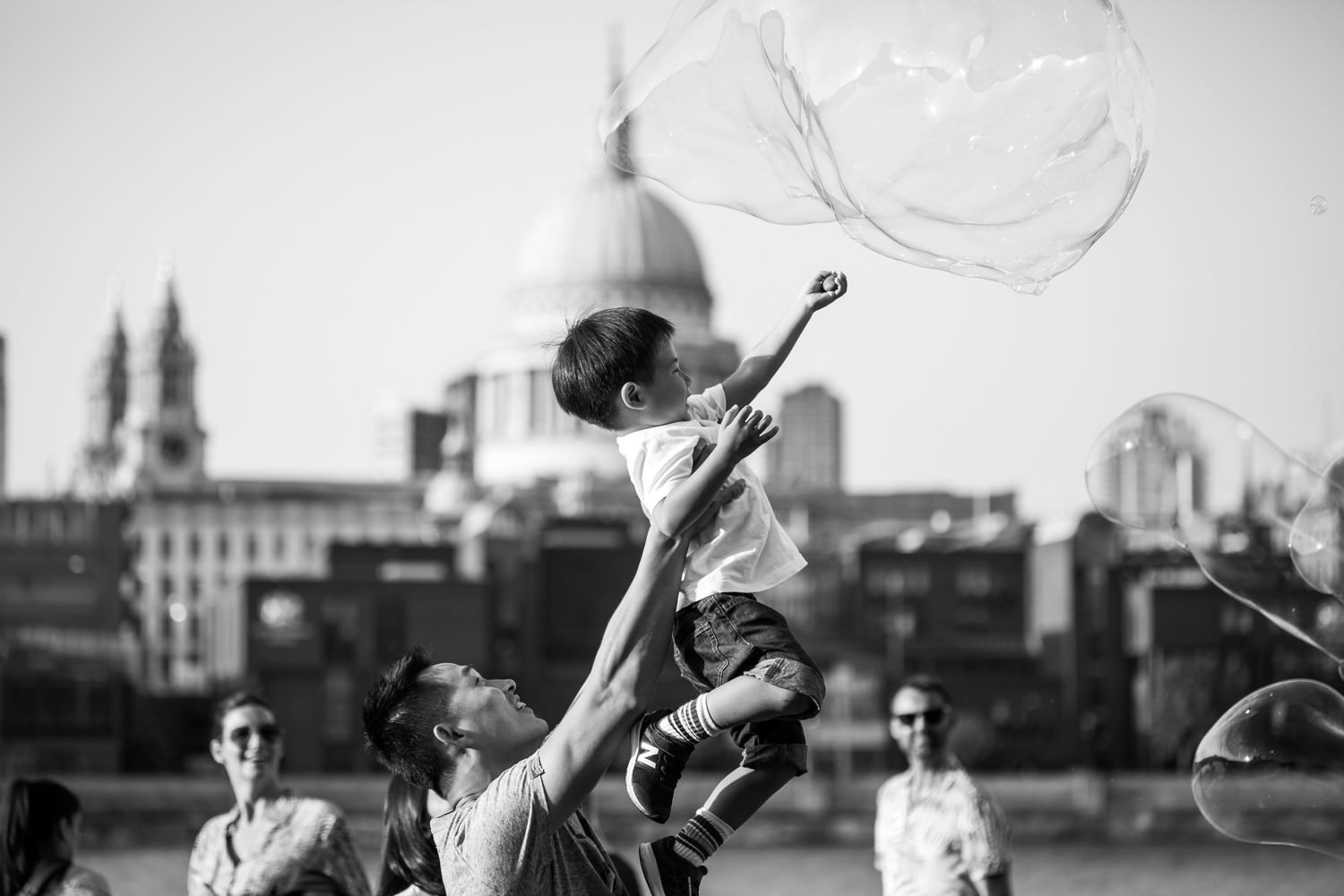 a black and white photograph of a boy playing with bubbles on South Bank