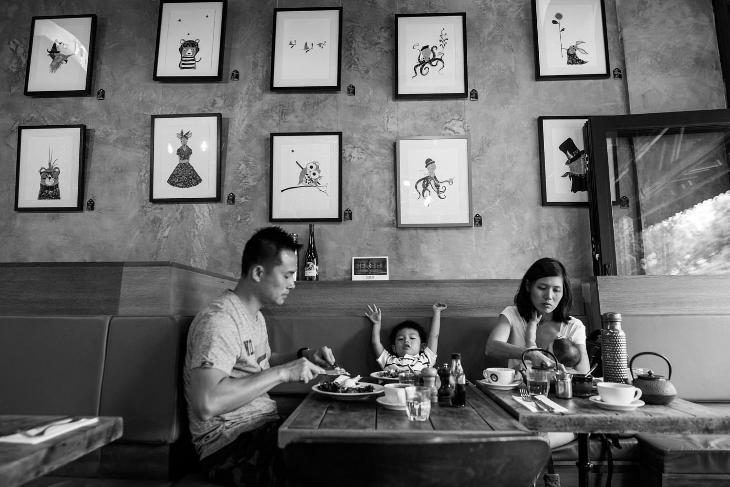 a black and white photograph of a family having breakfast in a cafe in Kensington
