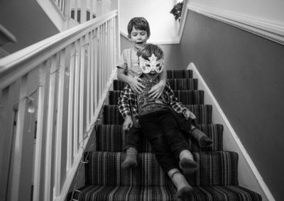 brothers riding down the staircase having fun