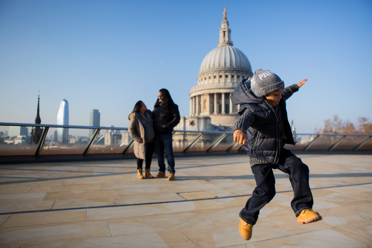 family photograph with boy jumping and St Paul's Cathedral in the background
