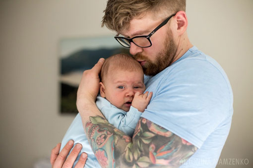 a colour photograph of a dad with a tattoo holding a newborn baby boy